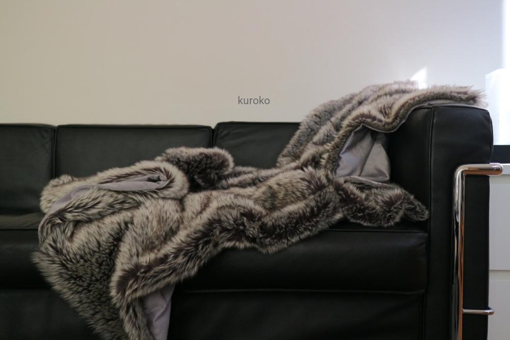 ソファーに掛けたラグジュアリーなフェイクファーのブランケット
